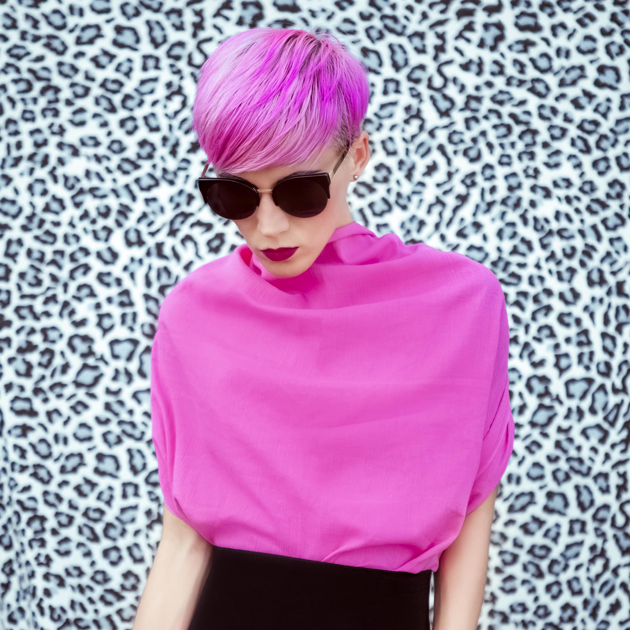 photo d'une jeune femme en rose avec une coupe de cheveux moderne et une chevelure rose